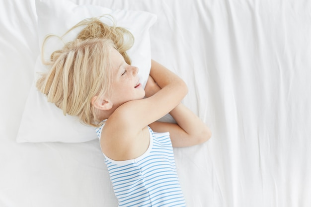 Menina bonita loira na camiseta de marinheiro, deitado no travesseiro branco, sorrindo enquanto dorme enquanto vê sonhos agradáveis. criança do sexo feminino repousante dormindo após um dia difícil, brincando com seus amigos. crianças, relaxamento