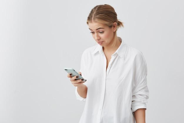 Menina bonita loira olhando com expressão de rosto confuso na tela do seu smartphone. bonita caucasiana fêmea vestindo camisa branca olhando confuso depois de ler a mensagem de sua amiga.