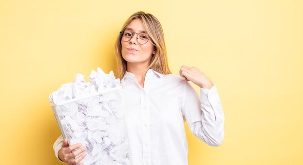 Menina bonita loira parecendo arrogante, bem-sucedida, positiva e orgulhosa. conceito de lixo de bolas de papel
