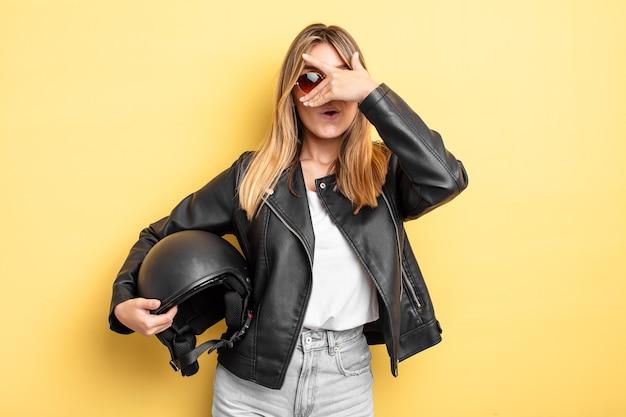 Menina bonita loira parecendo chocada, assustada ou apavorada, cobrindo o rosto com a mão. conceito de capacete de motocicleta