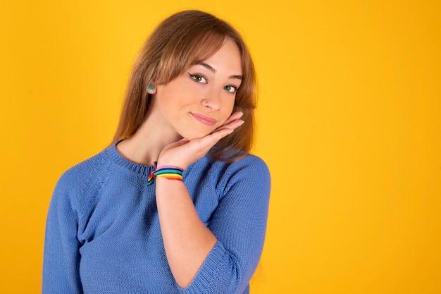 Menina bonita loira posando com pulseira de orgulho gay, feliz