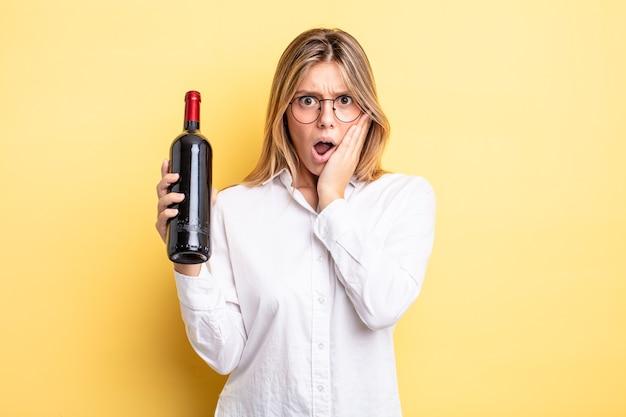 Menina bonita loira se sentindo chocada e com medo. conceito de garrafa de vinho