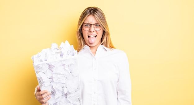 Menina bonita loira se sentindo enojada e irritada e com a língua de fora. conceito de lixo de bolas de papel