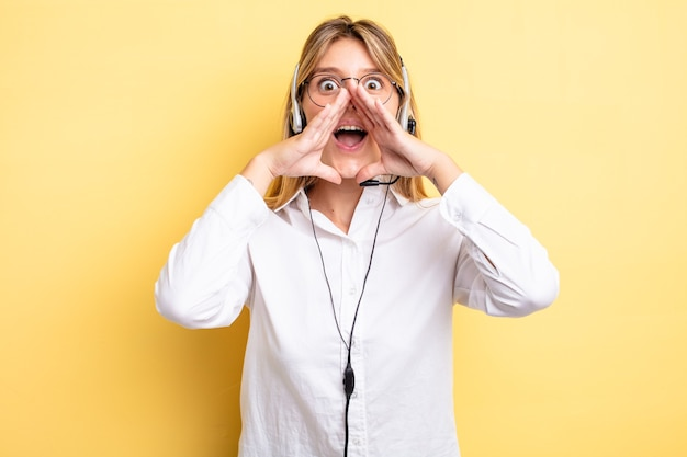 Menina bonita loira se sentindo feliz, dando um grande grito com as mãos perto da boca. conceito de fone de ouvido