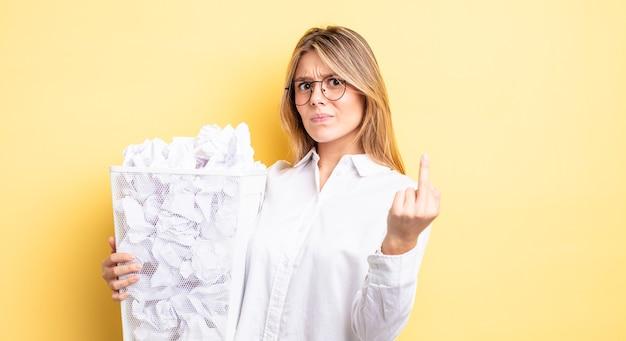 Menina bonita loira se sentindo irritada, irritada, rebelde e agressiva. conceito de lixo de bolas de papel
