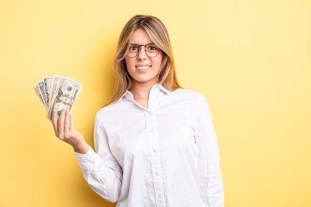 Menina bonita loira se sentindo perplexa e confusa. conceito de notas de dólar