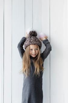 Menina bonita loira segurando bolas de neve