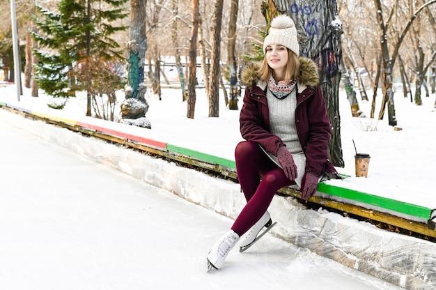 Menina bonita loira sentada no banco em dia de inverno