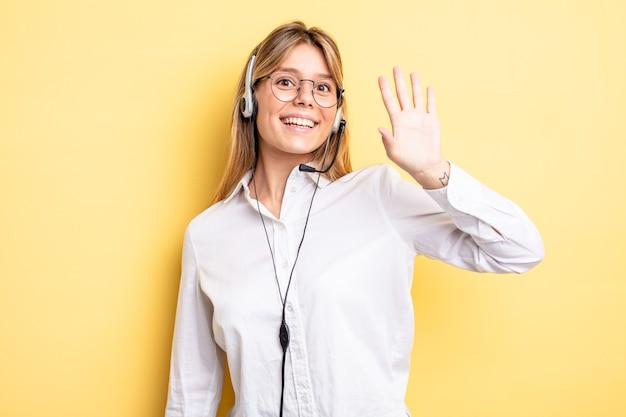 Menina bonita loira sorrindo alegremente, acenando com a mão, dando as boas-vindas e cumprimentando você. conceito de fone de ouvido