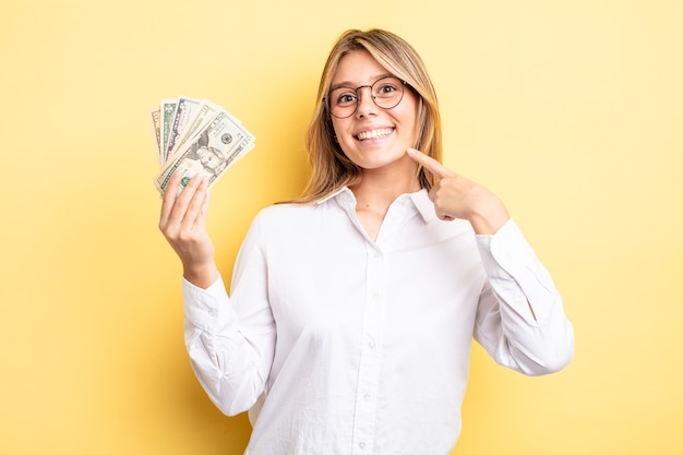 Menina bonita loira sorrindo com confiança, apontando para o próprio sorriso largo. conceito de notas de dólar