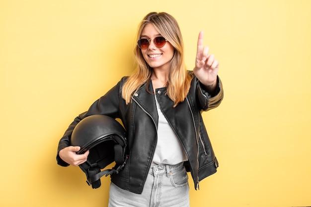 Menina bonita loira sorrindo com orgulho e com confiança, fazendo o número um. conceito de capacete de motocicleta