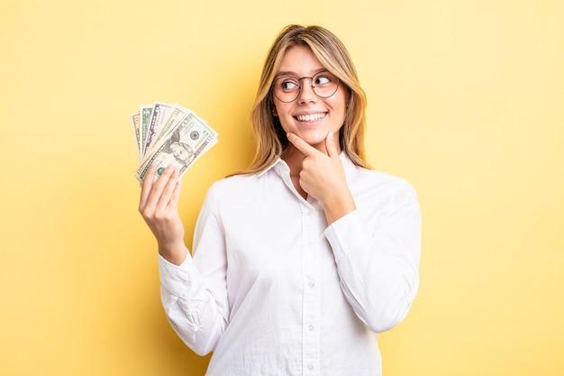 Menina bonita loira sorrindo com uma expressão feliz e confiante com a mão no queixo. conceito de notas de dólar