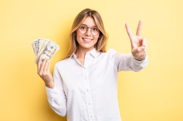 Menina bonita loira sorrindo e parecendo feliz, gesticulando vitória ou paz. conceito de notas de dólar