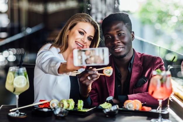 Menina bonita loira tirando uma foto ao telefone celular com sushi e mojito.