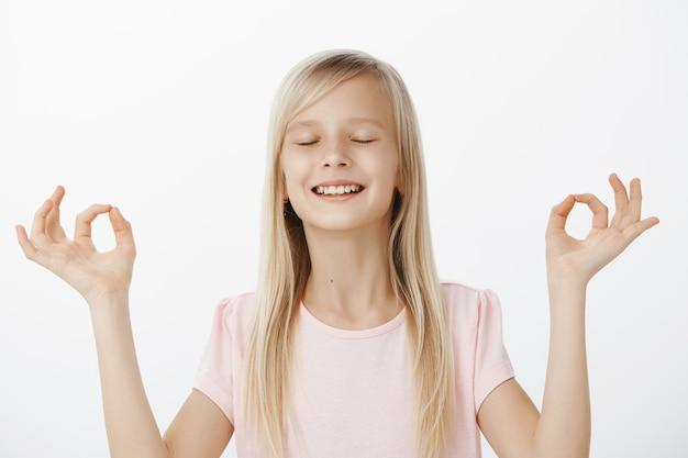Menina bonita meditando e sentindo-se calma. retrato de uma adorável adorável filha com cabelo loiro, fechando os olhos com uma expressão sonhadora, levantando as mãos com um gesto zen, fazendo ioga sobre a parede cinza