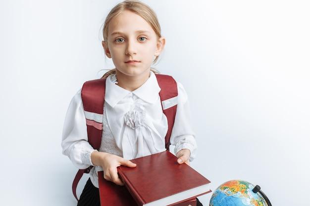 Menina bonita menina sentada com livros e um globo, sorrindo e feliz