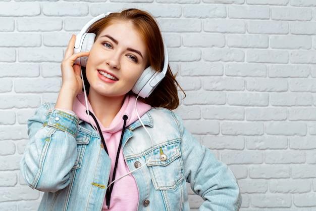 Menina bonita moda legal ouvindo música em fones de ouvido