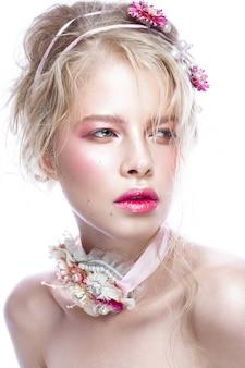 Menina bonita moda loira com flores no pescoço e no cabelo, maquiagem nude molhada