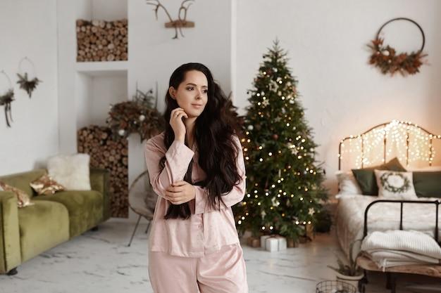 Menina bonita modelo com cabelo escuro e pijamas da moda posando decorada para o natal