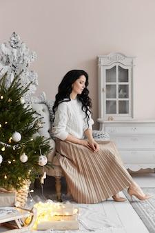 Menina bonita modelo com cabelos escuros vestindo saia e suéter branco no interior decorado para chris ...
