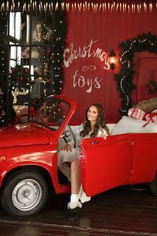Menina bonita modelo em vestido de malha posando em um carro vintage vermelho com decoração de natal e caixas de presente
