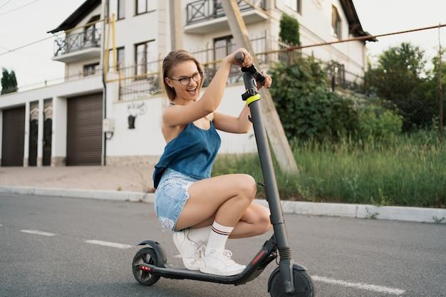 Menina bonita, montando uma scooter elétrica no verão na rua