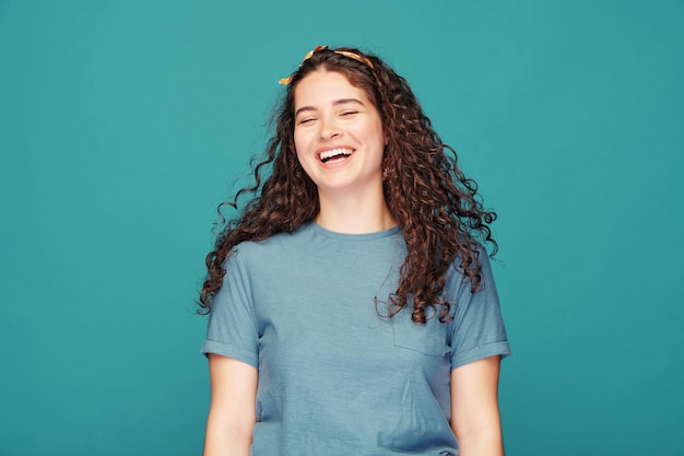Menina bonita morena com cabelos cacheados rindo alto no azul, conceito de emoção