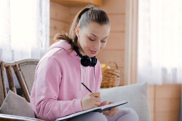 Menina bonita morena com fones de ouvido escreve no caderno em sua casa de campo