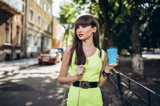 Menina bonita morena de vestido verde com uma xícara de café, caminhar ao ar livre na rua