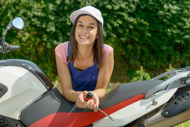Menina bonita morena em mecânica de motos