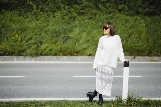 Menina bonita morena em pé ao lado da estrada