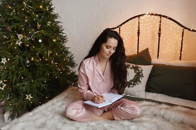 Menina bonita morena em pijamas aconchegantes, sentada na cama e escrevendo os planos de ano novo no caderno ao lado da árvore de natal.