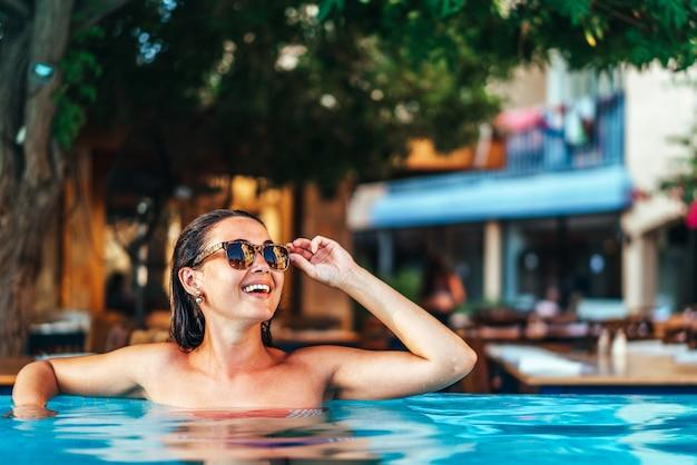 Menina bonita morena relaxante na piscina