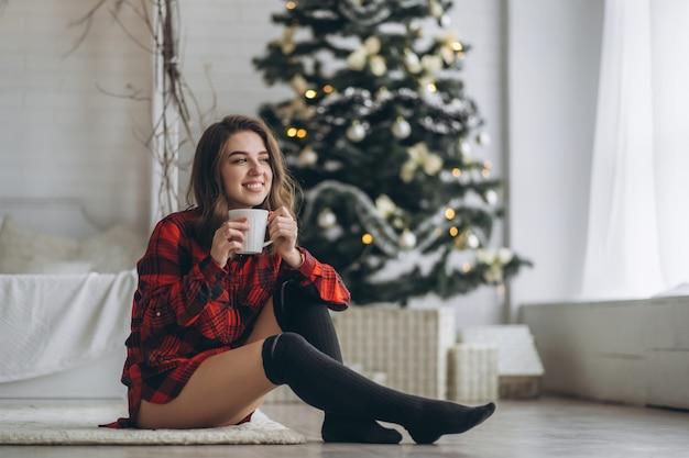 Menina bonita morena sentada no chão com uma camisa vermelha e meias com uma xícara de café e árvore de natal atrás