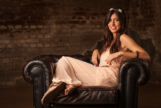 Menina bonita morena sentada no sofá de couro com fundo de parede de tijolo