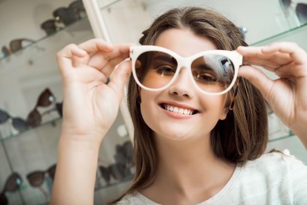 Menina bonita morena sorrindo, experimentando óculos de sol na loja de óptica