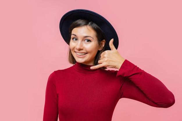 Menina bonita mostra gesto ligar para o telefone, em pé. pessoas, o conceito de linguagem corporal.