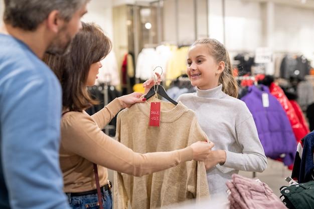 Menina bonita mostrando aos pais um pulôver de cashmere bege com desconto enquanto pede um novo item da casulawear durante as compras