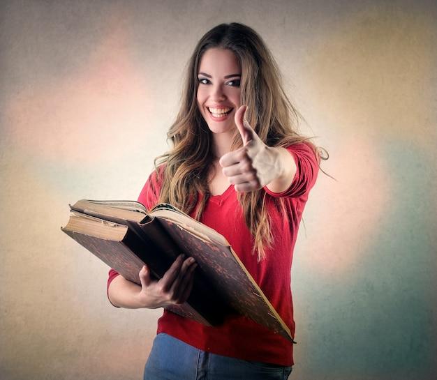 Menina bonita mostrando ok e segurando livros