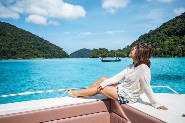 Menina bonita na cabeça lancha e olhando o belo mar na ilha de surin