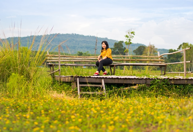 Menina bonita na cadeira de madeira em campo de flores amarelas