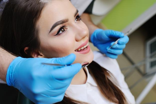 Menina bonita na cadeira odontológica no exame no dentista