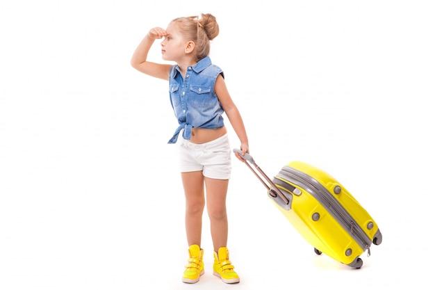Menina bonita na camisa azul, calções brancos e óculos de sol segurar amarelo suitcas