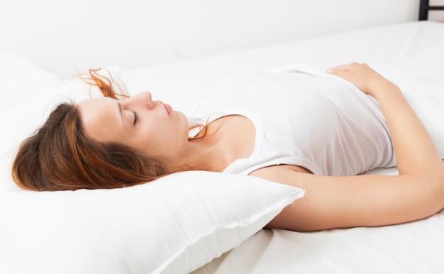 Menina bonita na camisa dormindo no travesseiro branco na cama em casa