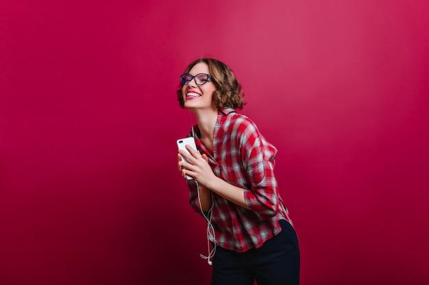Menina bonita na camisa quadriculada, rindo com os olhos fechados na parede clarete. foto interna de mulher de cabelo curto encaracolado emocional em copos segurando o telefone.
