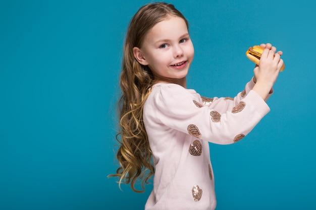 Menina bonita na camisola com cabelo moreno segurar um hambúrguer