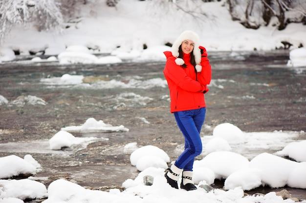 Menina bonita na floresta de inverno perto do rio.