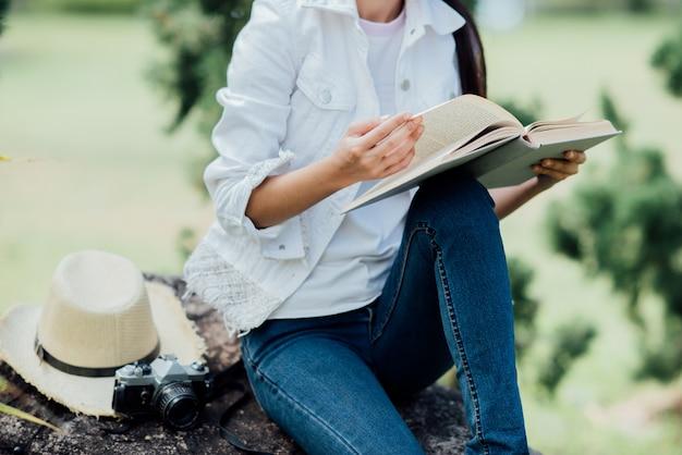 Menina bonita na floresta de outono, lendo um livro