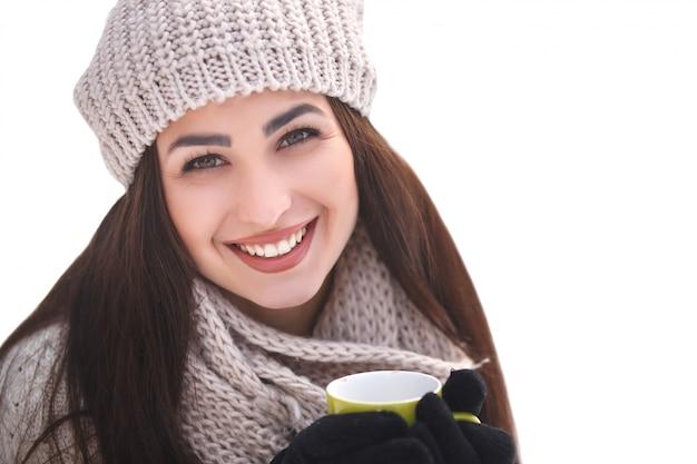 Menina bonita na floresta no fundo do inverno com uma xícara de chá.