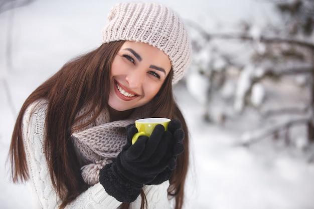 Menina bonita na floresta no inverno com uma xícara de chá.